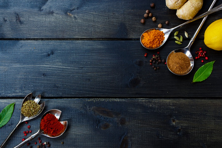 Achtergrond met kruiden en specerijen selectie op donkere houten tafel. Eten of koken concept. Bovenaanzicht.
