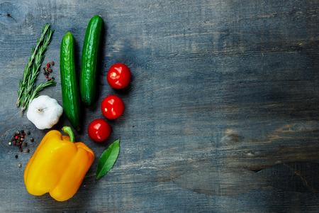 テキストのためのスペースと暗い背景の木の新鮮な野菜やスパイスの平面図です。ベジタリアン料理、健康、料理の概念。