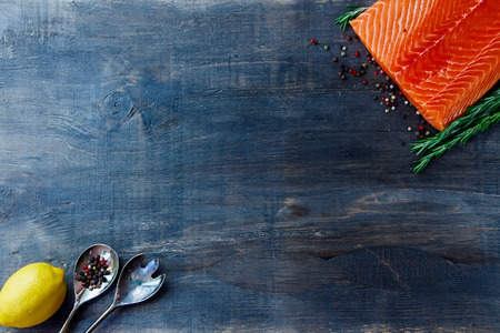 Delicious salmon fillet, aromatic spices and lemon on dark wooden background with space for text. Vegetarian food, health or cooking concept. Top view.