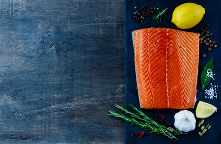 diet dinner: Top view of Fillet Salmon with aromatic spices and lemon on slate texture. Seafood on dark wooden background with space for text. Vegetarian food, health or cooking concept.