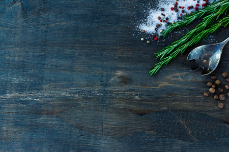 Top view of herbs and spices (rosemary, salt and pepper) on dark wooden background.