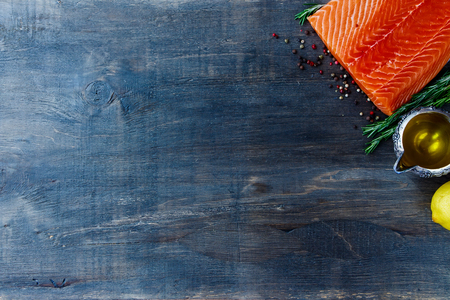 Seafood achtergrond. Rauwe filet zalm, olijfolie, aromatische kruiden en citroen. Ruimte voor tekst. Vegetarisch voedsel, gezondheid of koken concept. Bovenaanzicht. Stockfoto