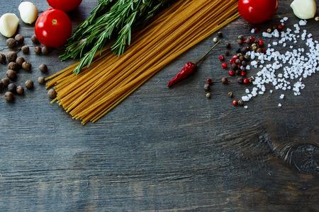 Achtergrond met Italiaans eten. Ingrediënten voor het koken over donkere houten bord (met gemakkelijk verwijderbare voorbeeld tekst).