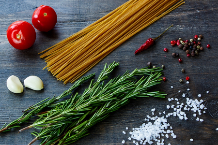 Food ingredients for italian pasta on dark wooden background.