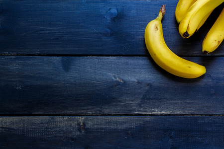 Fresh bananas on rustic wooden board. Healthy eating background with space for text.