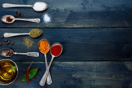 potherb: Ingredients background with olive oil, herbs and spices, old metal spoons and dark wooden board - cooking, healthy eating. Top view. Stock Photo
