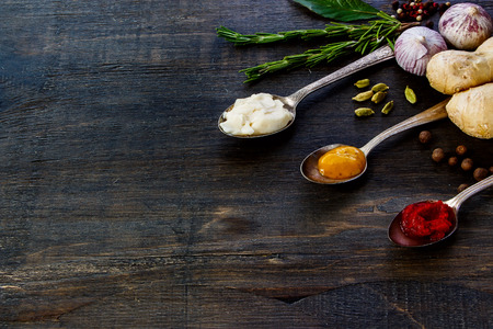 potherbs: Various Spices and Sauces on rustic wooden board. Cooking, food or health concept. Space for text. Stock Photo