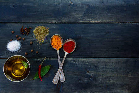 potherb: Healthy eating background - herbs and spices selection, old metal spoons and dark wooden background - cooking concept, top view.