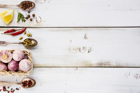 Witte houten achtergrond met knoflook, kruiden en specerijen selectie. Ruimte voor tekst. Koken, voedsel of de gezondheid concept. Stockfoto
