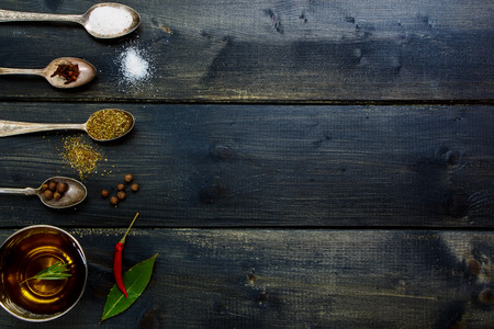 potherb: Ingredients - olive oil, herbs and spices, old metal spoons and dark wooden background - cooking, healthy eating. Top view.