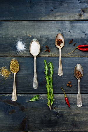 potherb: Food ingredients - herbs and spices, old metal spoons and dark wooden background - cooking, healthy eating. Stock Photo