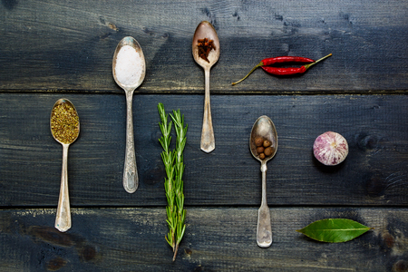 potherb: Top view of spices and herbs selection - herbs and spices, old metal spoons and dark wooden background - cooking, healthy eating Stock Photo