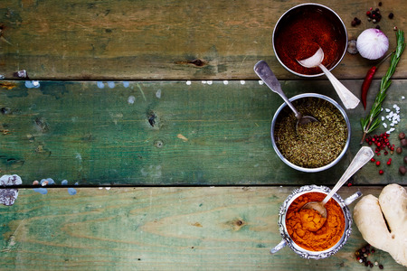 spice: Background with Spices. Herbs and spices selection - old metal cups and rustic wooden board. Cooking, food or health concept. Space for text