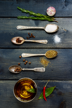 potherb: Top view of olive oil, herbs and spices, old metal spoons and dark wooden background - cooking, healthy eating. Top view.
