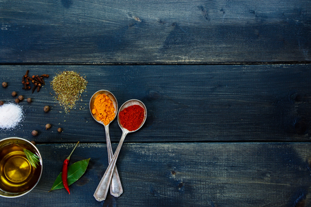 potherb: Herbs and spices selection, old metal spoons and dark wooden background - cooking, healthy eating. Top view. Stock Photo