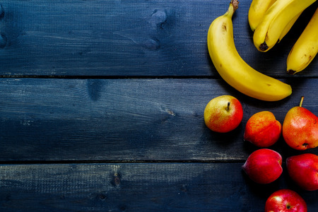 tropical fruits: Healthy eating background with fresh fruits on rustic wooden board. Space for text.