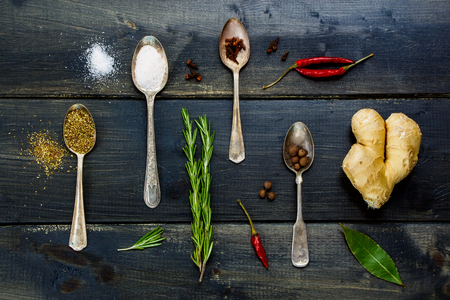 potherb: Top view of food elements - herbs and spices, old metal spoons and dark wooden background - cooking, healthy eating.