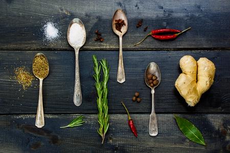 comidas saludables: Vista superior de los elementos nutritivos - hierbas y especias, cucharas de metal viejo y el fondo de madera oscura - la cocina, la alimentación saludable.