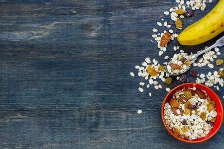 table grain: Healthy muesli for breakfast over dark wooden background with space for text. Health and diet concept. Stock Photo