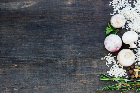Raw white rice with ingredients for risotto on dark wooden background with space for text. Vegetarian food, health or cooking concept.