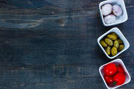 Ingredients for cooking (tomatoe, garlic, olives) on dark wooden background with space for text.Vegetarian food, health or cooking concept.