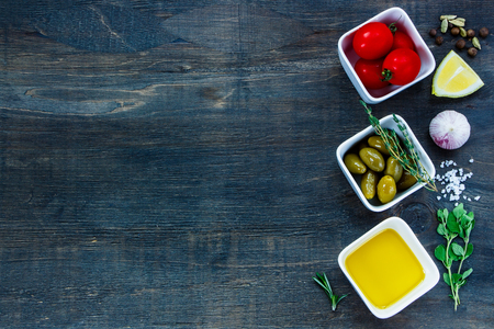 Ingredients for cooking (olive oil, tomatoe, garlic, olives, lemon, spices and herbs) on dark wooden background with space for text.Vegetarian food, health or cooking concept.