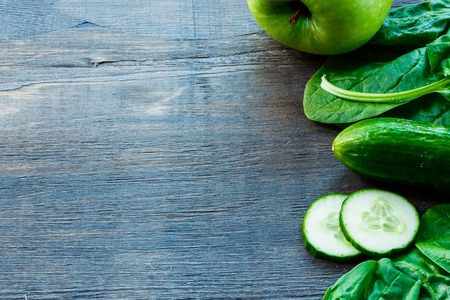 Mix of fresh green vegetables on dark wooden background with space for text. Detox, diet or healthy food concept. Stock Photo