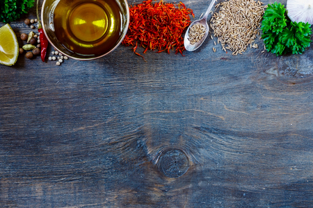 especias: Top view of herbs, spices, olive oil, salt and lemon on dark wooden background with space for text. Food and cuisine ingredients. Foto de archivo