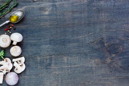 Verse paddestoelen met olijfolie, kruiden en specerijen op donkere houten achtergrond met ruimte voor tekst. Vegetarisch voedsel, gezondheid of koken concept.