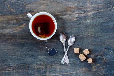 cuchara: Vista superior de la taza de té en el fondo de madera de la vendimia. Foto de archivo