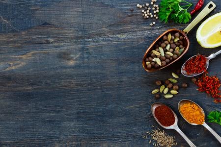 epices: Diverses épices dans la vieille pelle en métal et cuillères, herbes et épices sur fond de bois sombre avec espace pour le texte. Ingrédients de cuisine.