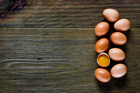 rustic food: Food background with eggs and one yolk over rustic texture. Top view. Space for text. Stock Photo