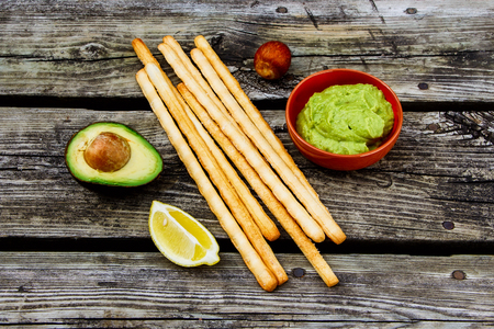 Food concept. Guacamole dip with bread sticks over rustic wooden background. Healthy snack.