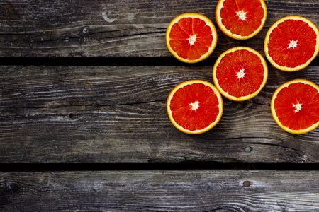 for text: Fresh bio oranges halves fruits on rustic wooden background with space for text.