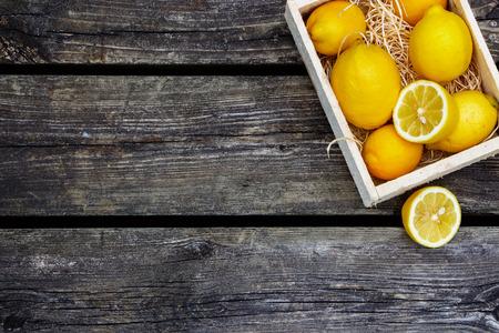 ジューシーな全体レモンとテキストのためのスペースを持つ素朴な木製の背景に新鮮なカットの半分。平面図です。