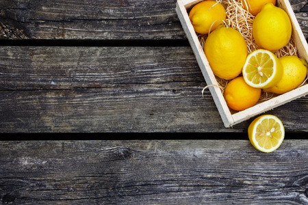 lemon: Juicy whole lemons and freshly cut half on rustic wooden background with space for text. Top view.