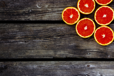 Healthy food. Fresh oranges halves fruits on rustic wooden background with space for text.