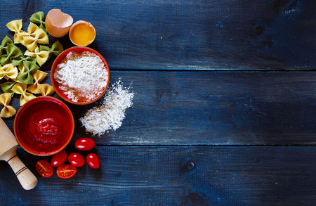 pasta sauce: Traditional Italian cooking with fresh pasta, sauce and ingredients on dark wooden background with space for text. Stock Photo