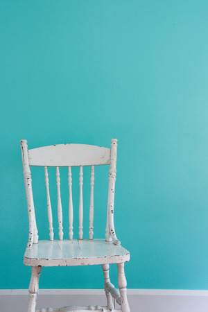 design objects: Old-fashioned white chair in front of a wall.