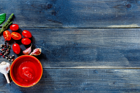 Background with tomato sauce ingredients (cherry tomatoes, fresh herbs, garlic, pepper) over dark wooden board.