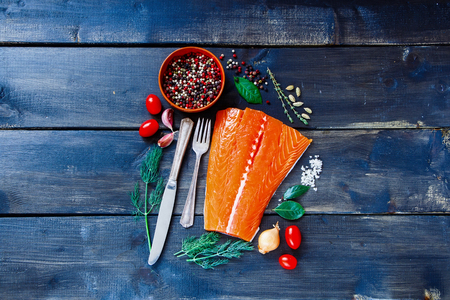 Food background with fresh salmon fish on dark wooden board.