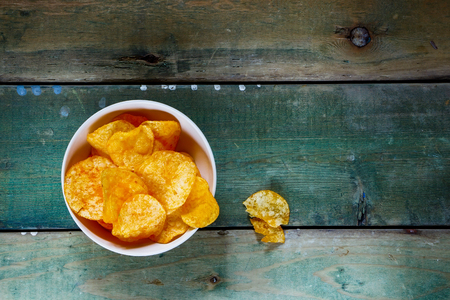 nacho chip: Top view of potato chips on old wooden background with space for text.