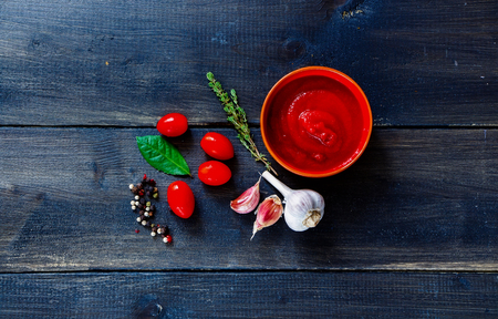 puree: Ingredients for tomato sauce (cherry tomatoes, fresh herbs, garlic, pepper) on dark wooden background. Stock Photo