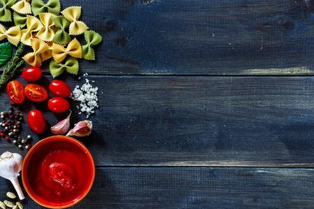 テキストのためのスペースと暗い背景の木のイタリア パスタ食材 (ミニトマト、パスタ、ニンニク、新鮮なハーブ、スパイス) の平面図です。