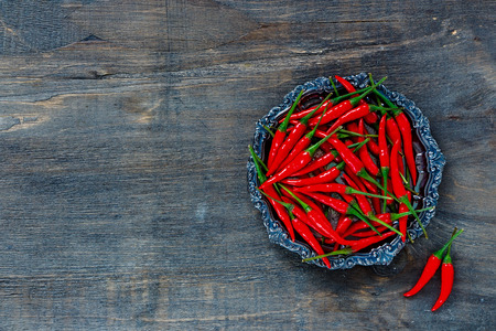 Top view of red hot chili peppers on vintage metal plate over dark wooden background with space for text.