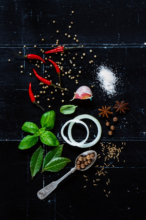 board: Top view of Various Fresh Herbs and Spices with Onion Slices and Hot Peppers on dark vintage background.