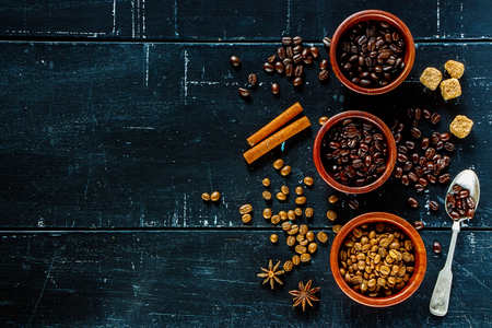 coffeetree: Three wooden bowls with different various of coffee beans on dark vintage background. Free text space. Top view.