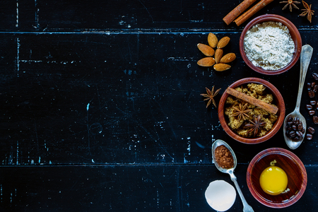 azucar: Ingredientes para la torta de hornear (harina, huevo, az�car moreno) en cuencos de madera en la cosecha de fondo oscuro con espacio para el texto. Vista superior.
