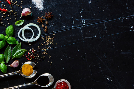 Various sauces in old metal spoons, fresh herbs and spices on dark vintage background with space for text.