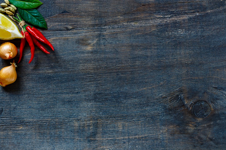wooden background: Top view on red hot chili peppers, onions, lemon and spices over dark wooden background with copyspace.